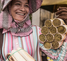 Woman Selling Rice Snacks Cooked In Bamboo Tubes, Skuon, Cheung Prey District, Kampong Cham Province, Cambodia