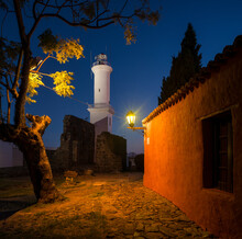 View Of Lighthouse At Night From Cobbled Street, Barrio Historico (Old Quarter), Colonia Del Sacramento, Colonia, Uruguay