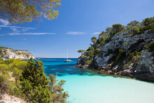 Coastal Bay And Distant View Of Yacht, Cala Macarelleta, Menorca, Spain