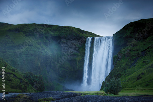 Skogafoss waterfall and grass covered mountains, Rangarvallasysla, Iceland - 376769074