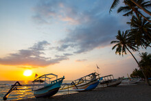 Silhouetted Fishing Boat And Palm Trees At Sunset On Senggigi Beach, Lombok, Indonesia