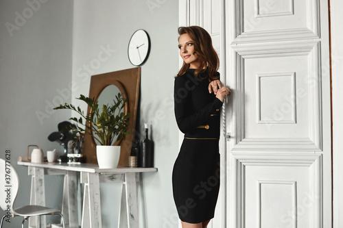 Fotografija Model girl with perfect slim body in a cocktail black dress posing near a vintag