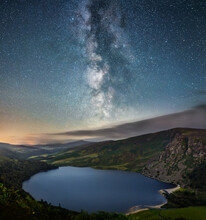 Scenic View Of Lake And Mountains Against Starry Sky At Night