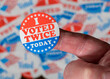Leinwandbild Motiv Finger with I Voted Twice button in front of many stickers given to US voters in Presidential election to illustrate vote fraud