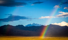 Scenic View Of Rainbow Over Red Rock Formation
