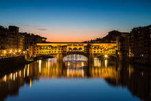 Illuminated Ponte Vecchio Bridge During Sunset