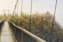 Tourist Walking On Mile High Swinging Bridge