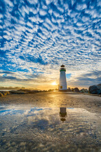Scenic View Of Walton Lighthouse Against Cloudy Sky During Sunrise