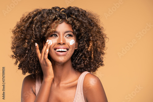 Fotografia Beautiful african girl applying a cream on cheek.