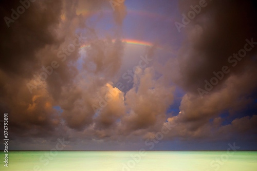View of stormy clouds and rainbow over Caribbean Ocean - 376793891
