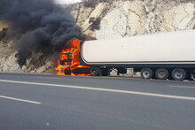 Burning Truck On The Road. Cab Of The Truck Is On Fire.