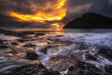 Waves Crashing On Rocks Against Hawaiian Coastline