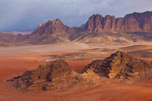 Scenic View Of Red Sand Desert And Sandstone Cliffs
