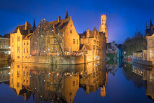 Scenic View Of Houses And Belfry Reflecting In Canal Water At Night