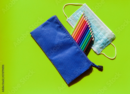 Back to school. Colorful image with children's case, color pencils and mask against covid 19