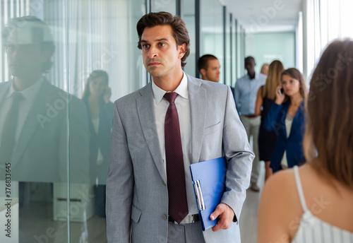 Portrait of focused successful businessman walking along busy office corridor Wallpaper Mural