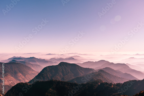 View of Himalayas mountain range with visible silhouettes through the colorful fog from Khalia top trek trail Fotobehang