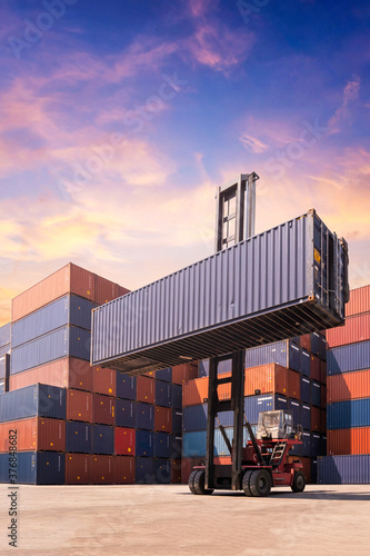 Fotografie, Obraz Forklift truck lifting cargo container in shipping yard or dock yard against sun