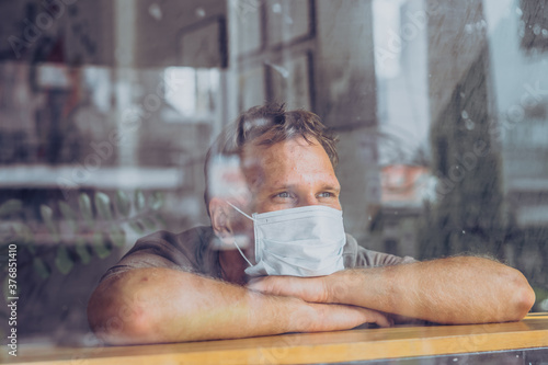 Obraz Man wear white protective mask, looking outside through window, afraid stress hope in eyes, recovery from the illness in home, self isolation due to global COVID 19 Coronavirus pandemic - fototapety do salonu