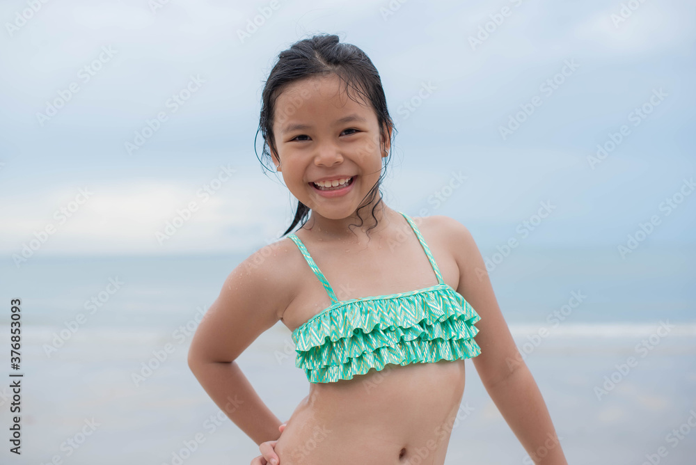 Fototapeta Little  girl playing on the beach on summer holidays. Children in nature with beautiful sea, sand and blue sky. Happy kids on vacations at seaside running in the water. .