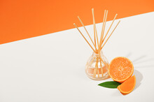 Air Freshener With Reed Sticks On A White Plate With Orange Tangerine. Room Aromatization With A Diffuser With A Natural Scent. Air Fragrance In A Transparent Bottle With Bamboo Sticks. Copy Space