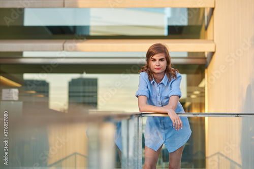 Valokuva Woman leaning against a glass railing outside