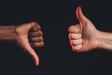 Like Dislike Gesture. Ethnic Diversity. Closeup African Male Hand Thumb Down Caucasian Thumb Up Isolated On Dark. Racial Disagreement