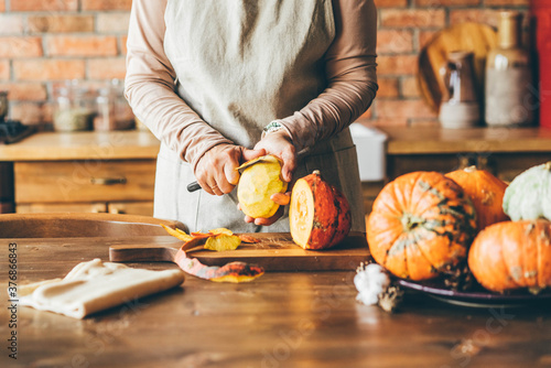 Foto Female hands with knife chopping pumpkin on cutting board