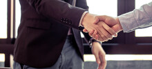Partners Shake Hands To Make A Deal, It Is A Picture Of The Working Atmosphere Of Company Employees In The Office In The Early 21st Century.