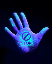 Stop The Spread Of Disease. A Human Hand Glowing From UV Ultra Violet Light Showing Bacteria And Viruses. Wash Your Hands Concept.