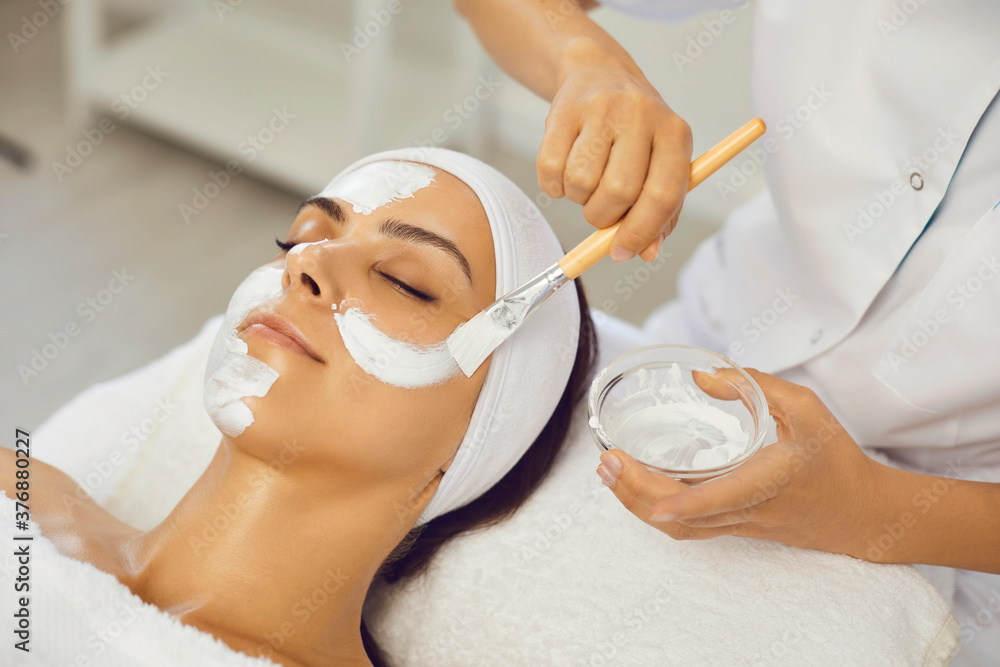 Fototapeta Cosmetologist smearing mask for serene woman in beauty spa salon