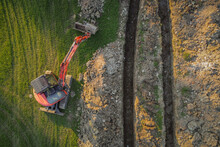 Aerial Drone View Of Geothermal Heating Collector Pit Or Trench In The Ground. Excavation Of Ditch Or Holes For Thermal Heat Exchanger For A House. Excavator On Work