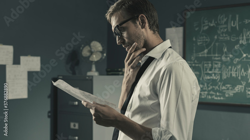 Young mathematician studying in his office and reading papers Wallpaper Mural