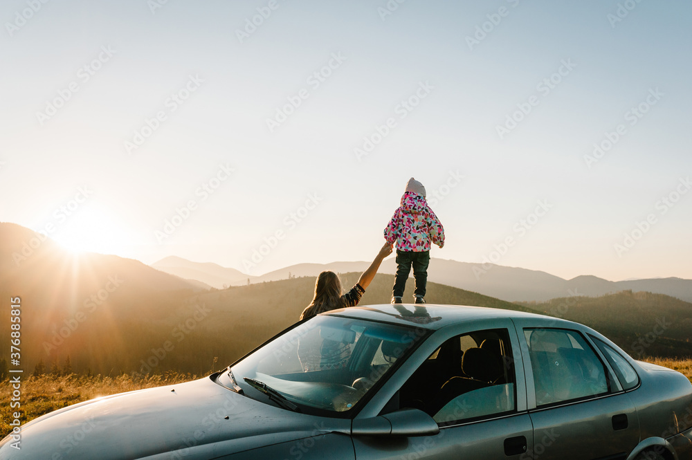 Fototapeta Mother and child in mountains on the sunset near car. Mom and daughter - tourist girls. Toward adventure! Family enjoying road trip on autumn vacation. Holiday and travel concept. Back view.