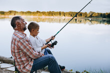 Grandfather And Grandson Fishing Outdoor On The Lake, Little Boy Looking At The Camera