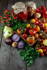 Tomatoes, peppers, onions on the table. Preservation of the autumn harvest of vegetables. Glass jar with pickled tomatoes. Wooden background. Vegetable food. Still life. Tomato of different varieties.