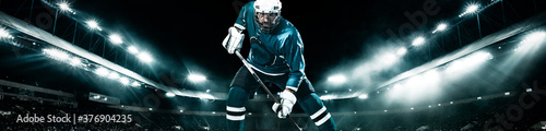 Fotografia Ice Hockey player athlete in the helmet and gloves on stadium with stick