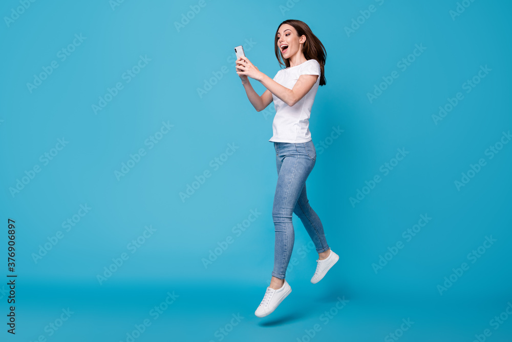 Fototapeta Full length body size view of her she attractive slim fit glad cheerful girl blogger jumping using cell app 5g fast speed dating service isolated bright vivid shine vibrant blue color background