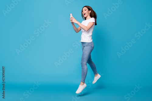 Fototapeta Full length body size view of her she attractive slim fit glad cheerful girl blogger jumping using cell app 5g fast speed dating service isolated bright vivid shine vibrant blue color background obraz