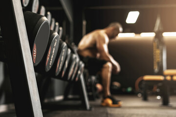Fototapeta na wymiar Dumbbells with free space and blurred bodybuilder on background
