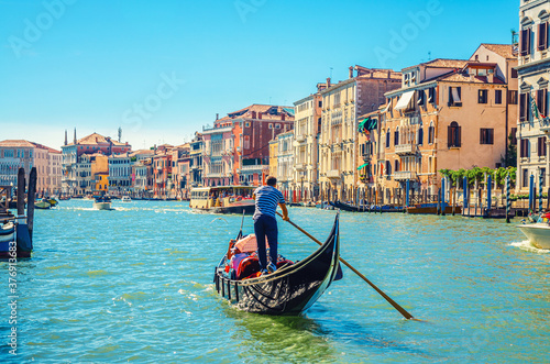 Obraz na plátně Venice cityscape with Grand Canal waterway, Venetian architecture colorful buildings, gondolier on gondola boat sailing Canal Grande, blue sky in sunny summer day