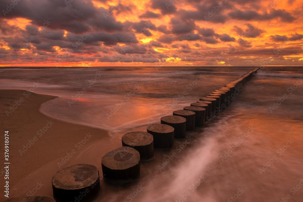 Fototapeta minimalist landscape showing sea waves and a breakwater at sunset