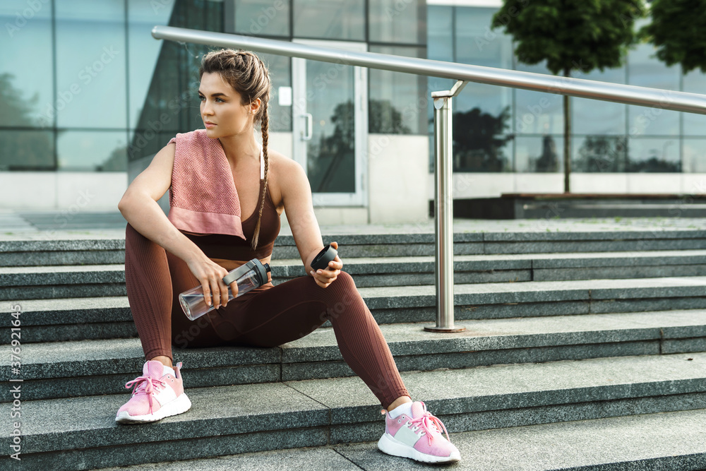 Fototapeta Sportive woman after fitness or jogging workout on a city street