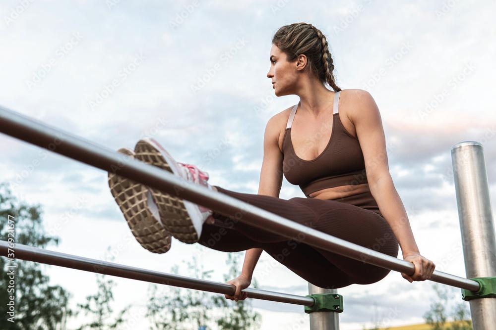 Fototapeta Woman athlete during calisthenics workout on a parallel bars
