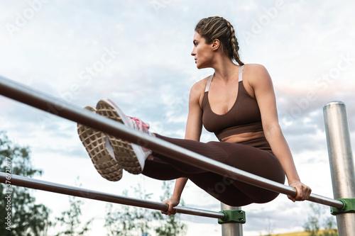 Fototapeta Woman athlete during calisthenics workout on a parallel bars obraz