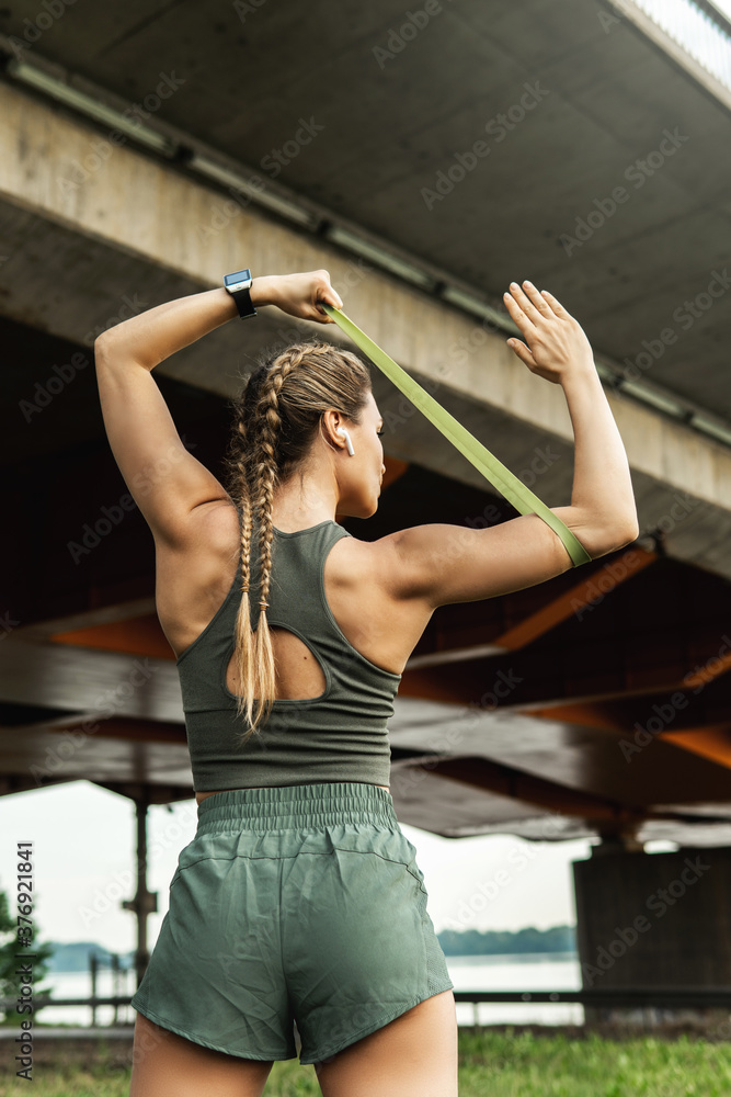 Fototapeta Athletic woman during workout with a resistance rubber band on a street