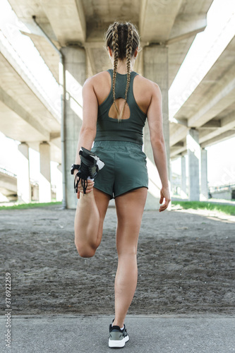 Sportive woman is stretching during fitness workout on a street