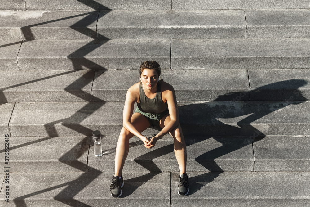 Fototapeta Confident sportive woman sitting on a stairs after fitness or jogging workout