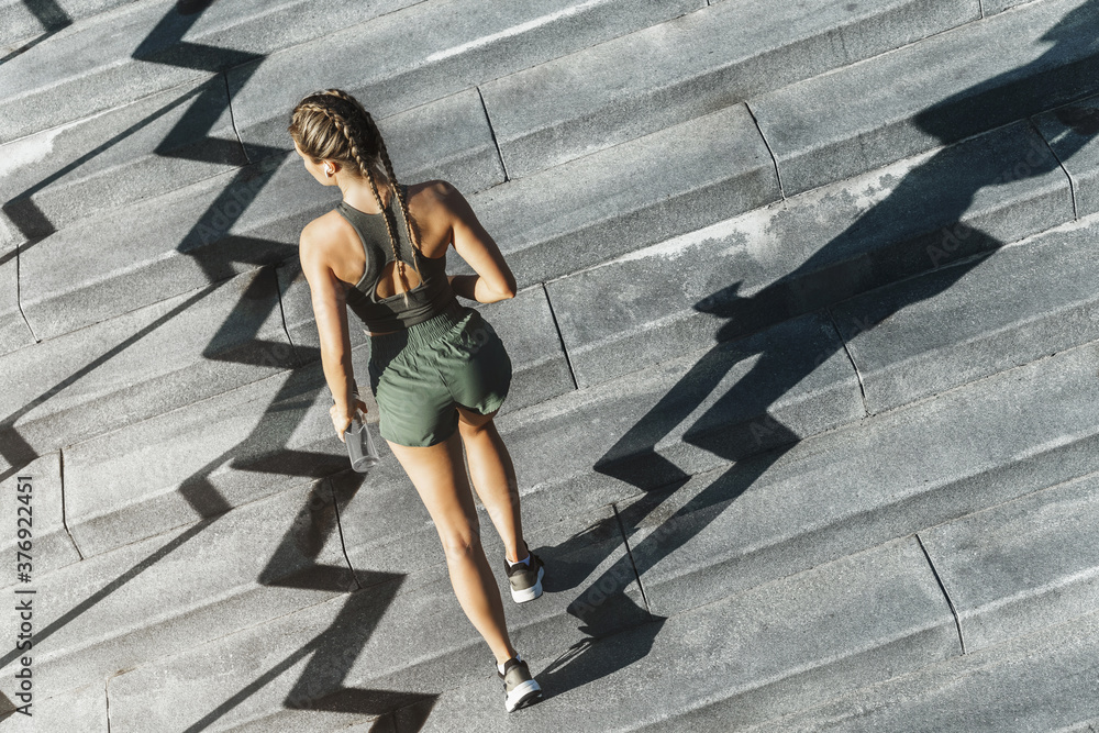 Fototapeta Sportive woman is running upstairs by a concrete staircase