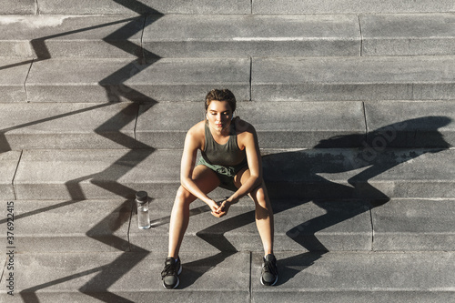 Fototapeta Confident sportive woman sitting on a stairs after fitness or jogging workout obraz